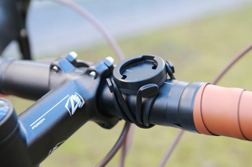 Le socle du compteur fixé sur le cintre de mon vélo par deux élastiques.